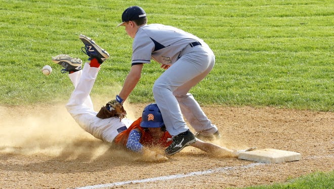 Edison's Andy Doland dives safely into third as the throw gets away from Notre Dame third baseman Erik Charnetski on Wednesday during the IAC South Large School Division tiebreaker at Edison.