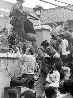 Mobs of South Vietnamese try to scale the 14-foot wall of the U.S. Embassy in Saigon, April 29, 1975, trying to reach the evacuation helicopters as the last of the Americans departed from Vietnam.