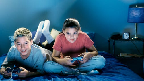 A tenage boy and girl play video games in this file photo.