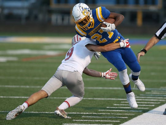 Irondequoit's William Porter is driven out of bounds after a reception by Canandaigua's John DiSalvo.