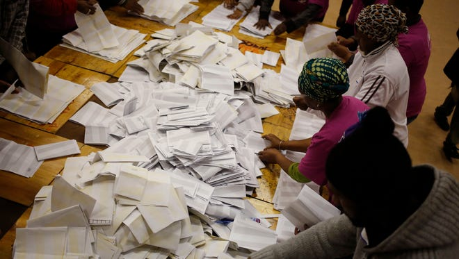 Election officials start the ballot counting process at a polling station during municipal elections in Manenberg on the outskirts of Cape Town, South Africa, Wednesday, Aug. 3, 2016.