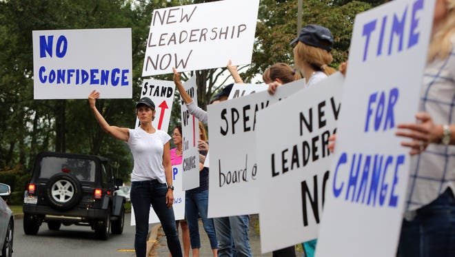 "Protester Jane Shepardson holds a ""No Confidence"" sign at a Sept. 19, 2016, rally outside the Chappaqua school district's administration building, asking for new leadership after the way Superintendent Lyn McKay handled the sex-abuse case of former teacher Christopher Schraufnagel."