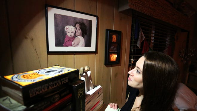 In this Feb. 13, 2017 photo, Casey Anthony looks up at a portrait of her with her daughter, Caylee, in her West Palm Beach, Fla., bedroom.