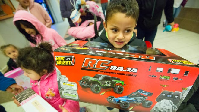Cesar Gonzalez, 5, of Las Cruces, holds on to his new remote control car that he picked out at the Doña Ana County Sheriff's Department toy giveaway on Saturday, December 23, 2017 at the County Government Center. Kids had their pictures taken with Santa and Mrs. Claus and then they had 30 seconds to pick out a toy from the toy room.