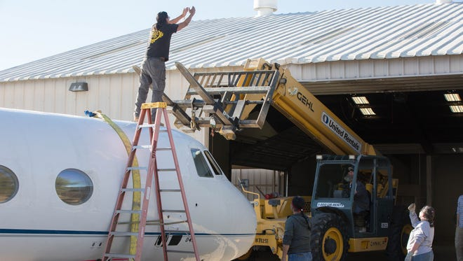 Crews with the IATSE Local 480 work to get a fuselage of a plane into the new Las Cruces Studios, Friday, March 2, 2018. The old Coca-Cola bottling plant south of town that has been vacant for years will soon be converted into a professional film studio, with 74,000 square feet of space.