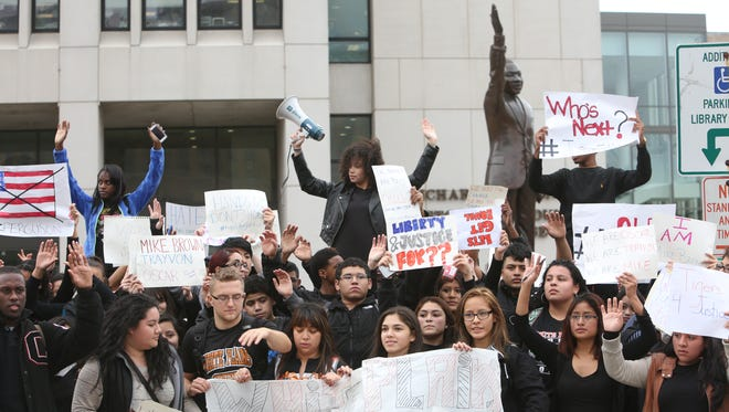 Students from White Plains High School raise their hands as they protest the grand jury's the decision in the Michael Brown case while outside the Westchester County Courthouse in White Plains.