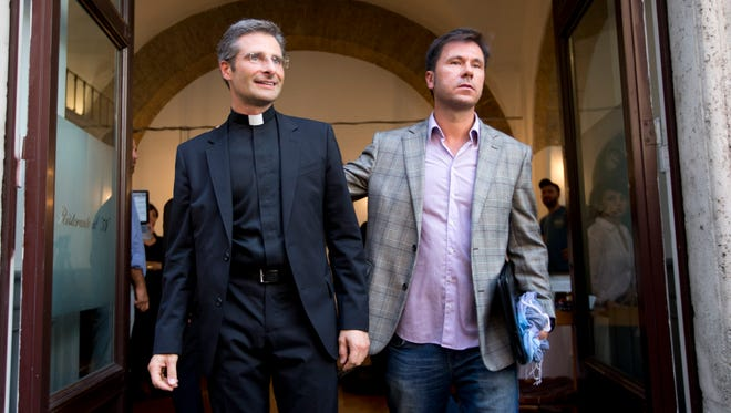 Monsignor Krzysztof Charamsa, left, and his boyfriend Eduard, leave a restaurant after a news conference in downtown Rome on Oct. 3, 2015.