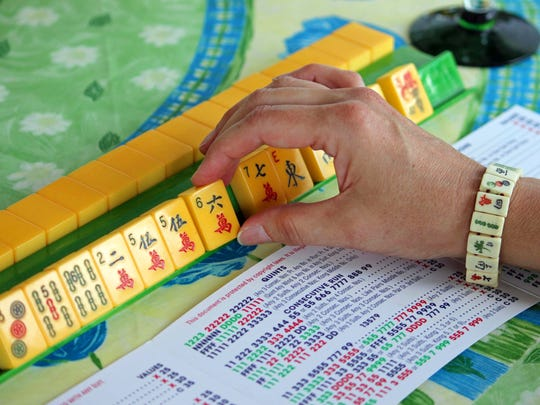 This May 31, 2013 photo shows a woman handling mahjong pieces during a game night gathering in Mayfield Village, Ohio. For the baby boomer generation, getting together to play games is a way to stay active and social. It also can help people stay mentally sharp.