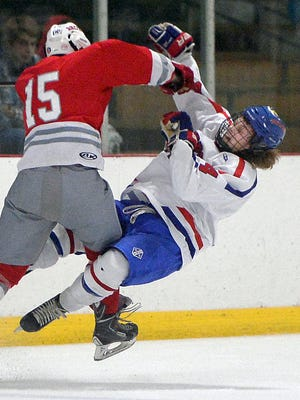 Fairport's Tristan Matthews, right, takes a hit from Canandaigua's Alex Burley at Thomas Creek Ice Arena on Dec. 12, 2015.
