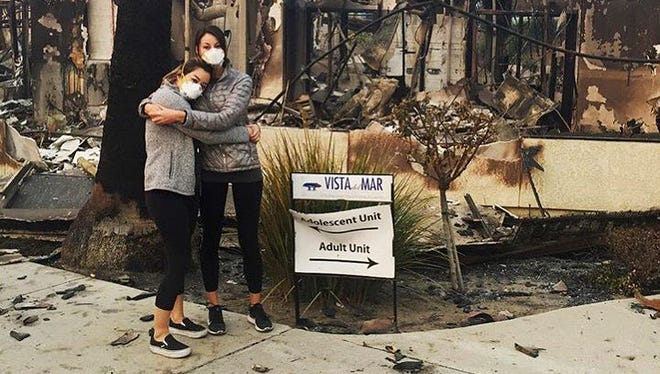 Former Vista Del Mar employee Jodi Ozaki stands with her friend Erin Tarkir in front of the burned hospital. The hospital's closure wiped out about two-thirds of psychiatric beds in Ventura County, sending patients and their families scrambling to find other care.