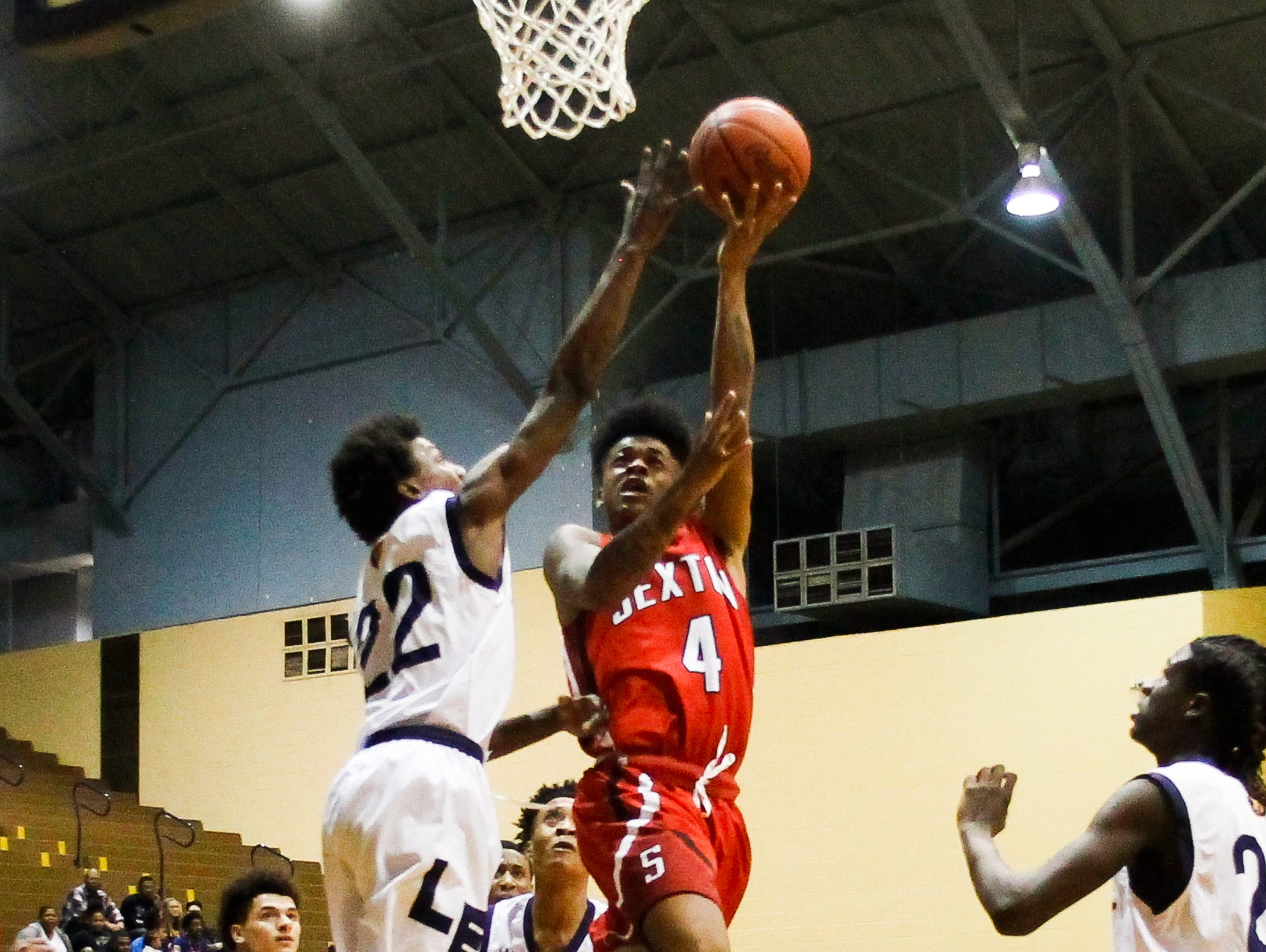 Sexton guard Marcus Alston drops in a layup from the paint against Lansing Eastern's Markiest Doss Friday, Feb. 24, 2017, at Don Johnson Fieldhouse in Lansing.