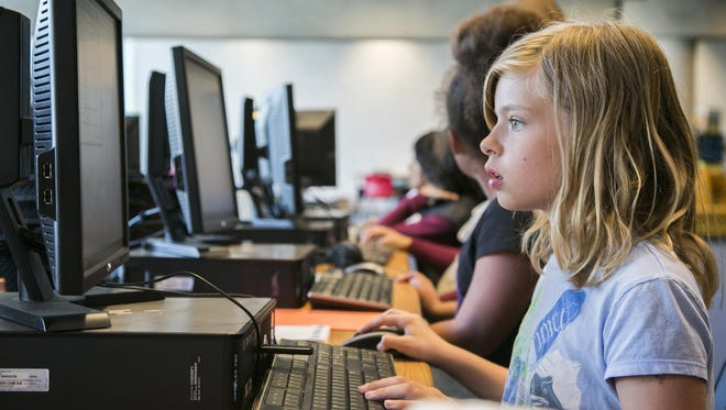 """Katelin Williamson, 10, works on her lines of code during """"Coderistas"""" at the Burton Barr Central Library in Phoenix, AZ on April 9, 2015."""