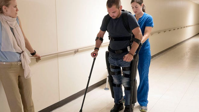 Isaac Schreurs uses a ReWalk exoskeleton to walk with physical therapist, Krista Henshue as physical therapy trainer from ReWalk, Lina Alsauskaite watches.