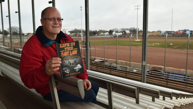 "Local auto racing writer and historian Joe Verdegan of Green Bay sits in the grandstands at Luxemburg Speedway with his new book, ""Life In The Past Lane: A History of Stock Car Racing in Northeastern Wisconsin from 1950-1980."" The book will be released Saturday, and Verdegan will sign copies at Titletown Brewing in Green Bay."