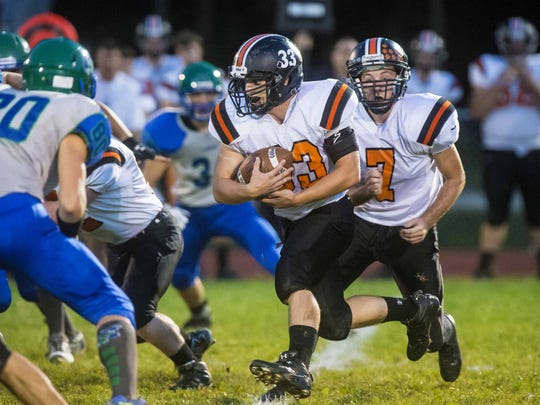 Middlebury's Cortland Fischer charges the line against Colchester in Colchester on Friday, September 18, 2015.