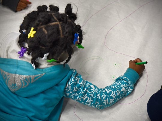 A homeless child works on an art activity during a SMART Kids activity Thursday, March 24, at the St. Cloud Salvation Army shelter.
