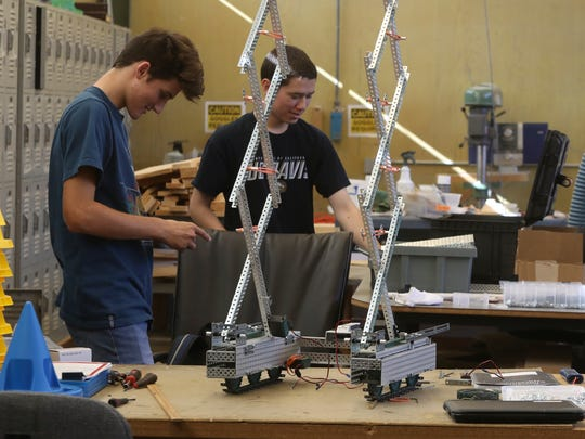 Central Valley High School students Orion McNames, from left, and Rickey Sell work on their competition robot Tuesday at the school in Shasta Lake.