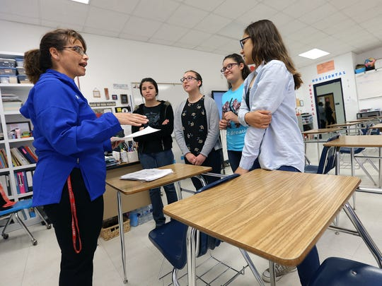 Clint Early College Academy math teacher Carlota Alvarez Basurto gives students a critique on their math project during her conference period Wednesday.