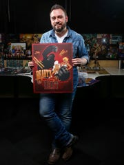 """Anthony """"Ant"""" Lucia, an artist and illustrator from Des Moines, holds a poster he illustrated featuring King Kong. Lucia has been illustrating DC Comics characters for the DC Bombshells series from his studio on Grand Avenue."""