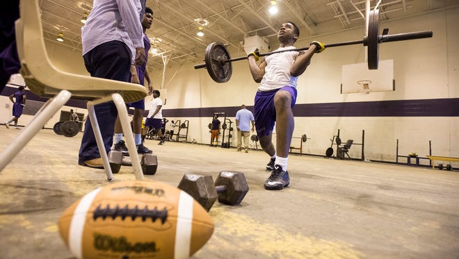 Trezevant High School football players including Tijuan Mason, 16, exercise in the weight room on April 1, 2015, after their field practice was cancelled due to heavy rain. Mason verbally committed to Purdue on Monday.
