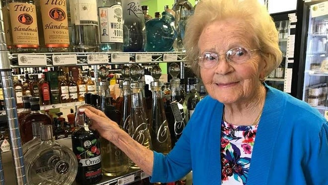 Hedy Steinbart, 92, of Lansing, picks up a bottle of Oma's Cherry Vodka at Vine & Brew in Okemos. Her grandson launched the brand using her recipe. It is now for sale in Michigan.