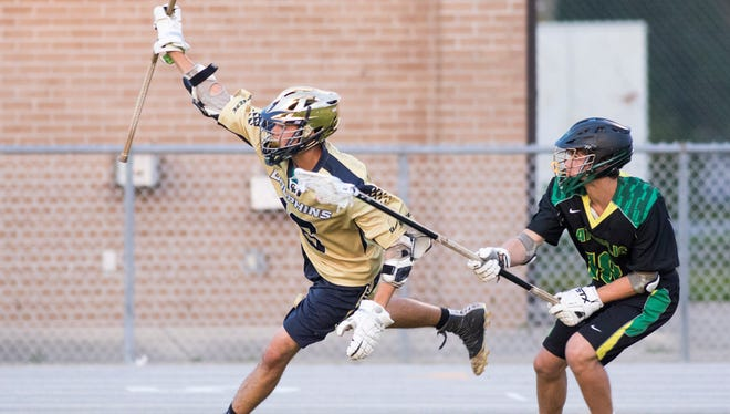 Tucker Smith (16) tracks down the ball and tries to stay in bounds during the boys district 1 lacrosse championship game between Gulf Breeze and Catholic high schools at Gulf Breeze High School on Friday, April 20, 2018.