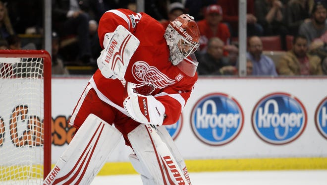 Petr Mrazek attempts to clear the puck during the Red Wings' 5-4 shoot-out win over the Senators at Joe Louis Arena on April 3, 2017.