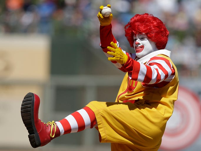 A man dressed as Ronald McDonald throws out the ceremonial first pitch before a spring exhibition baseball game between the Texas Rangers and the Kansas City Royals on March 22 in Surprise, Ariz.