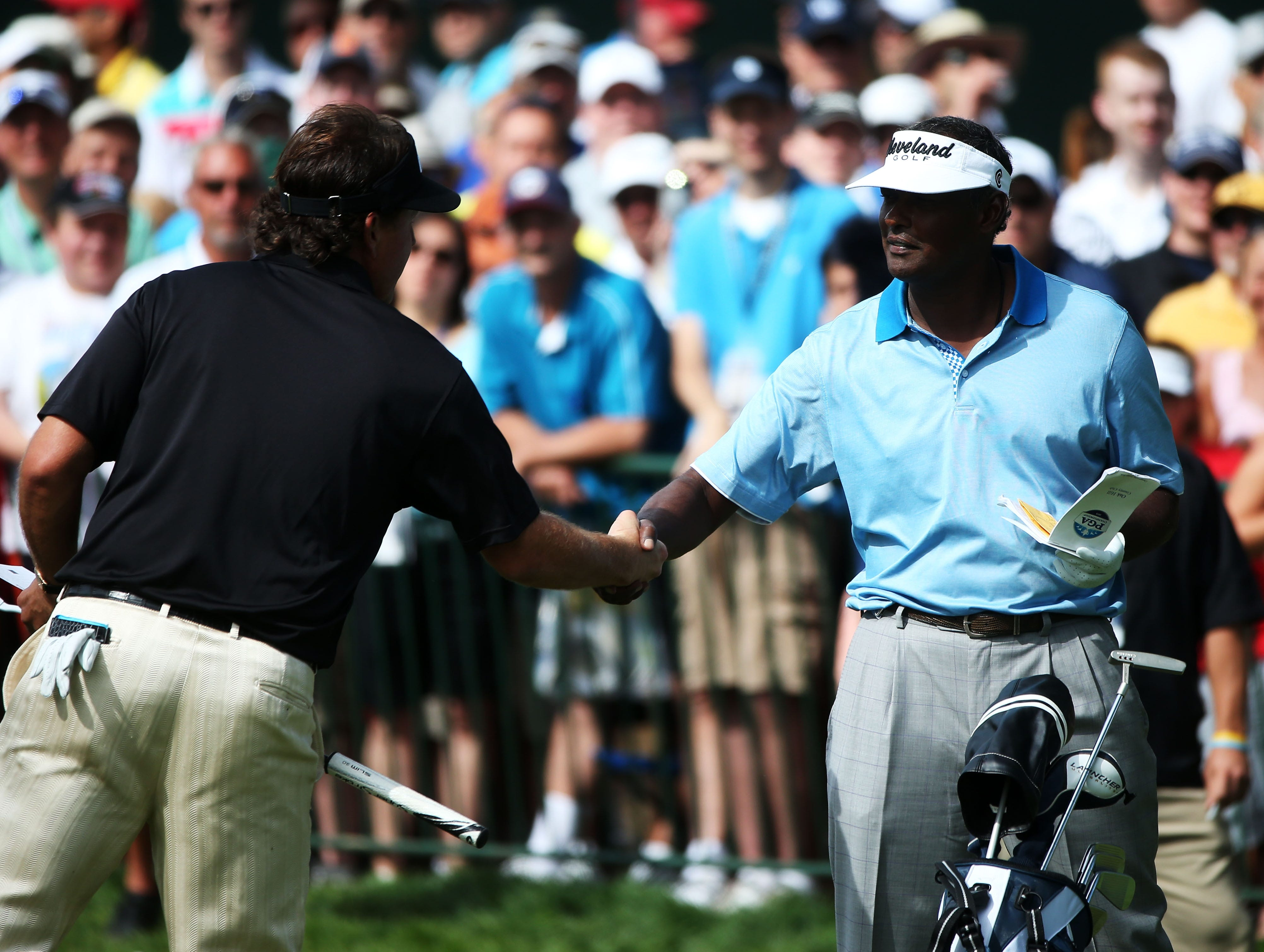 Vijay Singh (R) and Phil Mickelson (L) shake hands on the first hole.