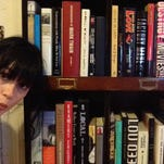 Here I am in front of one of the many bookshelves in my apartment.