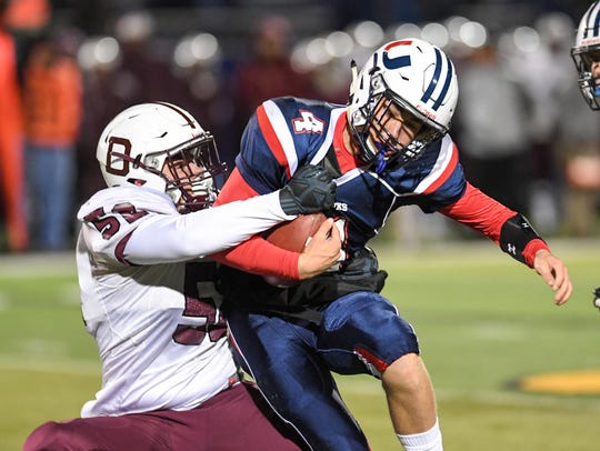 Dowling's Nate Colins (52) flies in for a sack on Urbandale