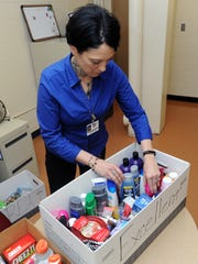 Brandy Morris-Hafner, administrator of the Ross County day reporting program, goes through boxes of items she gives out as part of the program Thursday, Feb. 23, 2017, at the Terry Collins Reentry Center.