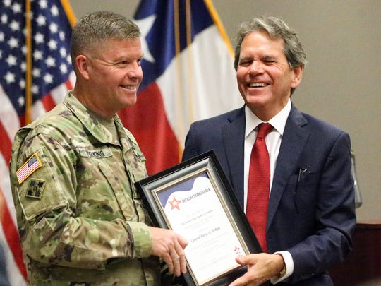 Gen. David G. Perkins is presented with a proclamation by Jack Chapman, board chairman for the Greater El Paso Chamber of Commerce, saying the star on the Franklin Mountains would be lit in Perkins' honor Wednesday.