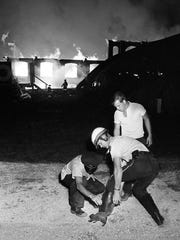 Officials are recapturing a squirrel that escaped both it cage and the fire at the Tennessee State Fair Sept. 20, 1965. The roaring fire is burning out of control as it is destroying the ancient four-building exhibition area complex on opening night of the fair.