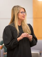 Judge J.J. Frydrychowicz talks about the inspirational coin that is presented to the graduates during the TEAM Court graduation ceremony in Pensacola on Wednesday, May 10, 2017.
