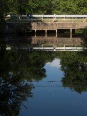 School children walk over Jones Creek on the way to