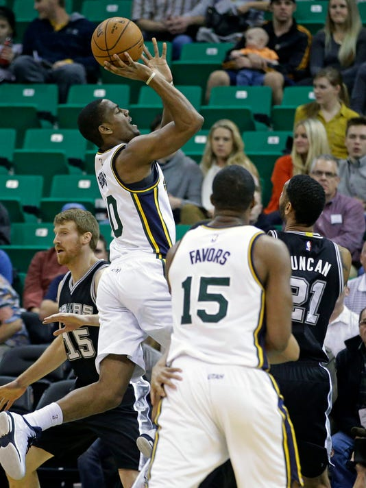 Utah Jazz's Alec Burks (10) shoots as San Antonio Spurs' Tim Duncan (21) and Utah Jazz's Derrick Favors (15) look on in the first quarter during an NBA basketball game Tuesday, Dec. 9, 2014, in Salt Lake City.  (AP Photo/Rick Bowmer)