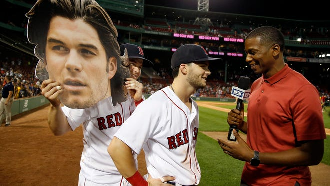 Boston Red Sox's Brock Holt holds up a picture of Andrew Benintendi as he is being interviewed by NESN's Jahmai Webster after their 8-4 win over the Texas Rangers in a baseball game Tuesday, July 10, 2018, in Boston. (AP Photo/Winslow Townson)