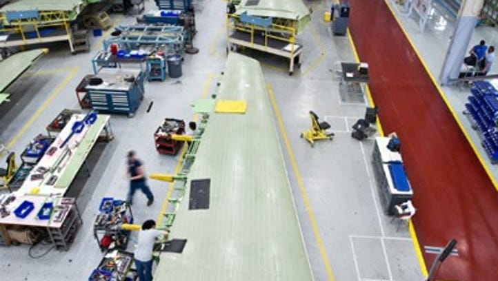 Workers work on the Gulfstream G450 wing box at the Triumph Aerostructures plant on Vultee Boulevard.