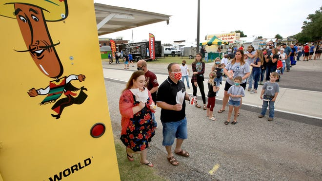 Sarah and Shawn Jensen pick up their Pronto Pups for lunch during the Food and Tunes event at the Kansas State Fair on Friday.