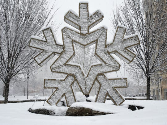 A snowflake sculpture covered in actual snow sits atop the fountain near the Vance Monument downtown.