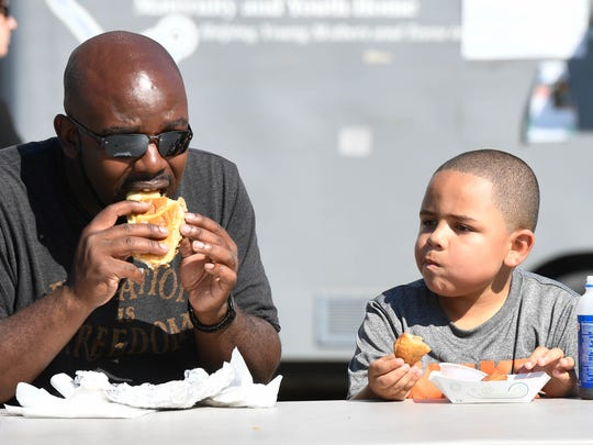 Lemarceo Shemwell and his son Cameron Shemwell, 11 years-old, enjoy philly steak and cheese and deep fried pizza for lunch as the lunch time crowd fills West Franklin Street for the Evansville West Side Nut Club Fall Festival Thursday, October 6, 2016