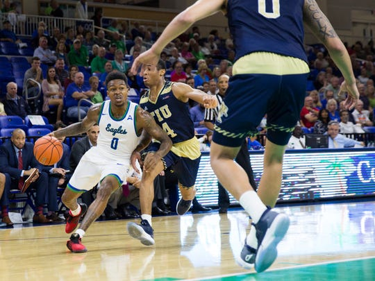 Florida Gulf Coast University junior, Brandon Goodwin, drives to the basket as Florida International University sophomore, Kimar Williams, attempts to defend during the game against Florida International University on Sunday, December 11, 2016 at Alico Arena in Estero, Fla.