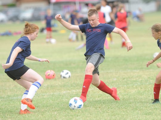 Caleb Gaule, center, kicks the ball during a drill at the Full Pitch Soccer Academy on Sunday, June 3, 2018 at Madison Middle School.