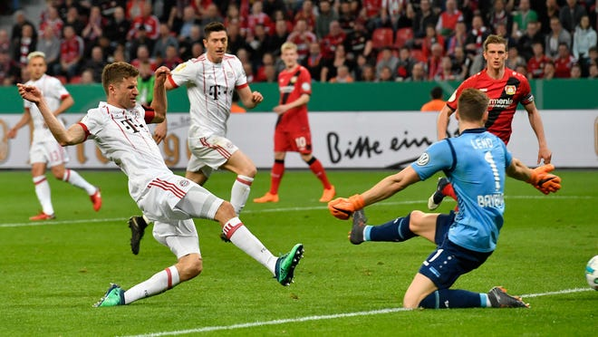 Bayern's Thomas Mueller scores his side's third goal during the German soccer cup semifinal match between Bayer Leverkusen and Bayern Munich in Leverkusen, Germany, Tuesday, April 17, 2018. (AP Photo/Martin Meissner)