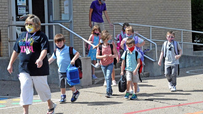 Students are escorted to their bus for the trip back home from Wooster Township Elementary, Triway District, after the first day of the 2020-21 school year Wednesday.