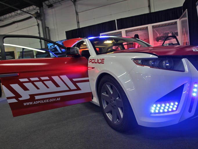 With flashing lights and Arabic wording on its side, the Carbon Motors E7 concept car is shown at Key Auctioneers, Wednesday, January 22, 2014.  The futuristic police cruiser is being auctioned off Thursday, January 23, 2014, at the 5520 S. Harding St. auction house at 1pm.  The last place the car was shown was in Dubai, so the writing on the side was changed for the location, put in Arabic script.
