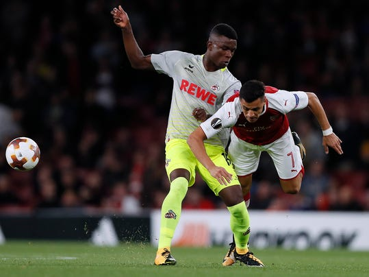Arsenal's Alexis Sanchez, right, and Cologne's Jhon Cordoba challenge for the ball during the Europa League group H soccer match between Arsenal and FC Cologne at the Emirates stadium in London, England, Thursday, Sept. 14, 2017 . (AP Photo/Kirsty Wigglesworth)