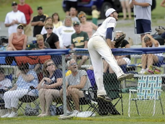 West York's Kaden Hepler leans over the fence while trying to catch a foul ball during the Bulldogs' semifinal victory