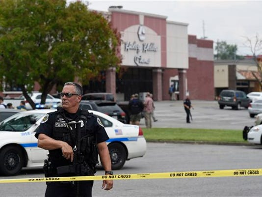 An officer stands in front of the Carmike Hickory 8 movie theater following a shooting Wednesday, Aug. 5, 2015, in Antioch, Tenn.